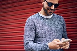 Cheerful bearded male with dimple wearing warm knitted sweater and sunglasses browsing smartphone and smiling while standing against red wall