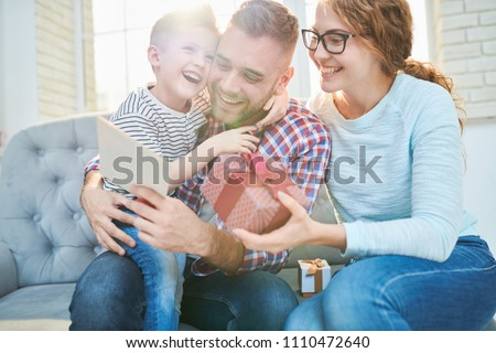 Cheerful bearded man embracing his cute little son while reading handmade greeting card for Fathers Day, his pretty wife sitting next to him and holding gift box in hands