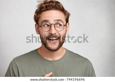 Cheerful bearded man enjoys every day, looks with glad expression aside, wears casual clothes, has trendy hairstyle. Delightful male student has good mood after seminar, isolated over white wall #744196696