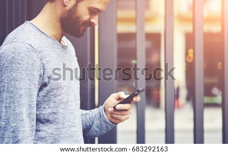 Cheerful bearded man messaging online with friends on mobile phone connecting to high speed 4G internet standing on street.Male blogger browsing websites.Copy space area for advertising text message #683292163