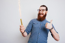 Cheerful bearded man showing thumbs up and celebrating success with fire works