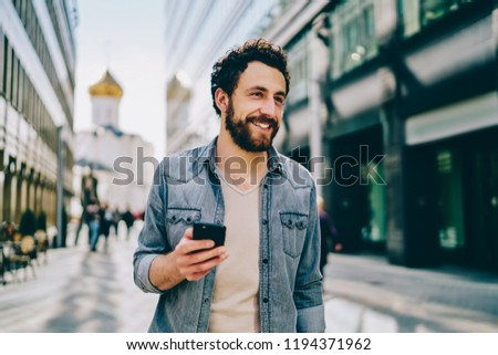 Cheerful bearded 30s young man dressed in denim wear looking away while holding smartphone using 4G internet connection. Happy hipster guy holding mobile phone while walking outdoors on city street