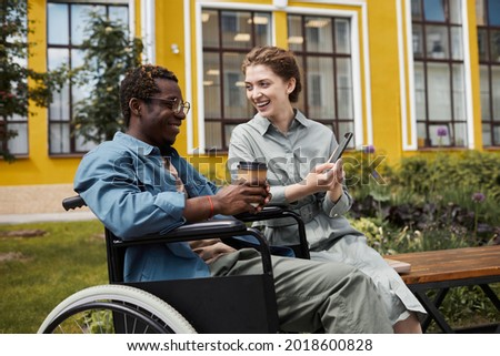 Cheerful beautful woman sitting on bench and sharing funny video with disabled biyfriend during stroll Photo stock ©