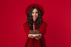 Cheerful beautiful brunette girl in hat showing birthday cake isolated over red background
