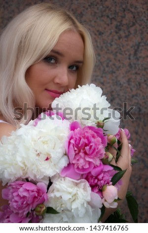 Cheerful, beautiful, cheerful, blue-eyed girl with white hair smiling at the photographer. Close-up. Portrait of a girl with a bouquet of flowers. #1437416765