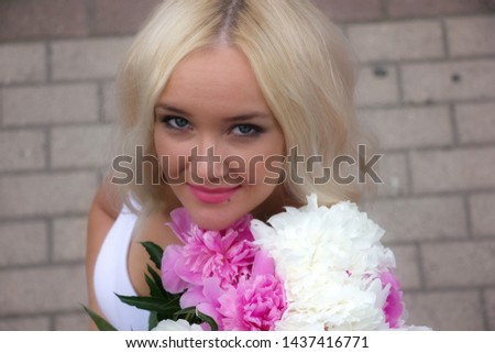 Cheerful, beautiful, cheerful, blue-eyed girl with white hair smiling at the photographer. Close-up. Portrait of a girl with a bouquet of flowers. #1437416771
