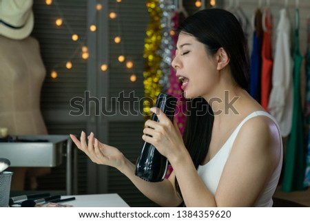 cheerful beautiful japanese woman singer singing while drying hair with blowdryer sitting at mirror vanity table. aisan entertainer practice songs for performance show concert by hair dryer backstage