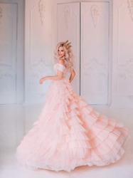 Cheerful beautiful princess girl blonde laugh smiling. Luxury ballroom evening elegant trendy tulle pink dress fluttering fly motion. Happy cute face Queen. woman enjoy holiday. Backdrop white room