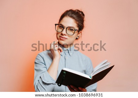 Cheerful beautiful young woman wearing eyeglasses in casual smiling and holding a notebook in hand