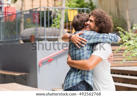 Shutterstock Cheerful best friends embracing each other outside coffee shop. Two young multiethnic guys hugging each other. Happy smiling best friends meeting each other after a long time with a hug.