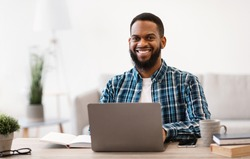 Cheerful Black Businessman Sitting At Laptop Smiling To Camera Working Online On Computer In Modern Office. Entrepreneurship And Own Business. Successful Career Concept. Selective Focus