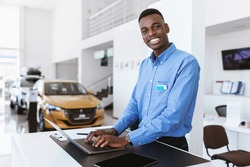Cheerful black car salesman posing at work desk, smiling at camera, typing on laptop in auto dealership. Happy African American automobile manager in showroom store, copy space