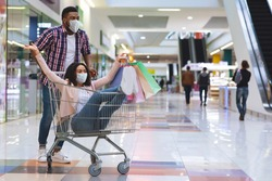 Cheerful black couple in medical face masks having fun while shopping in mall, making purchases during coronavirus pandemic, playful man pushing trolley with his girlfriend inside, copy space