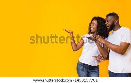 Cheerful Black Couple Is Pointing Away At Free Space, yellow background, panorama #1458159701