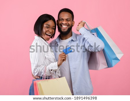 Cheerful black couple with credit card and shopping bags, buying gifts for Valentine's Day remotely on pink background. Positive young guy and his girlfriend encouraging contactless payment