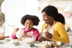 Cheerful Black Family Mother And Daughter Baking Together In Kitchen. Cute Little African American Girl Adding Ingregients To Bowl While Preparring Dough For Cookies With Mom At Home, Free Space