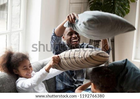 Cheerful black family spend free time weekend have a fun together. American laughing father hold pillow play fight with little preschool cute daughter and son sitting on couch in living room at home