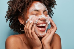 Cheerful black female model applies foaming cleanser, has clean fresh healthy skin, smiles broadly, Afro bushy haircut, stands bare shoulder against blue background. Beauty and feminine concept