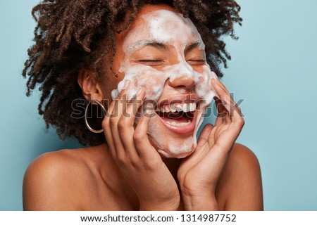 Cheerful black female model applies foaming cleanser, has clean fresh healthy skin, smiles broadly, Afro bushy haircut, stands bare shoulder against blue background. Beauty and feminine concept #1314987752