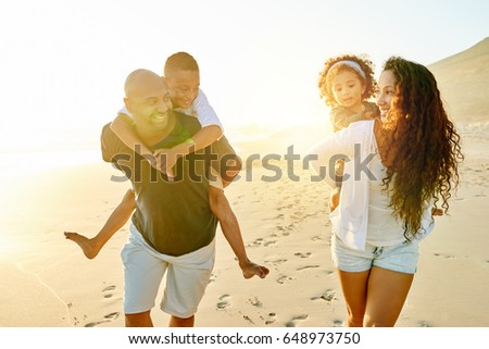 Cheerful black man and woman walking and carrying their children in evening sandy shore. #648973750