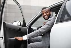 Cheerful black man in expensive suit getting in luxury car, holding door and smiling at camera. African american successful entrepreneur going to office in the morning