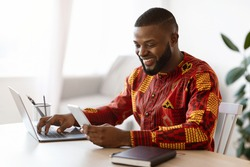 Cheerful Black Man In Traditional African Clothes Using Smartphone And Laptop