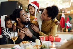 Cheerful black parents and their kids having fun while spending Christmas together at home.