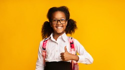 Cheerful Black School Girl Gesturing Thumbs-Up Smiling To Camera Posing Over Yellow Studio Background. I Like School Concept. Panorama