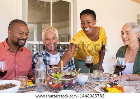 Cheerful black woman serving bowl of fresh salad to guests during lunch. Mature woman serving food while family members enjoying lunch with wine. Happy senior couple and african couple having lunch.