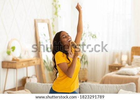Cheerful black woman with hairbrush as mic singing her favorite song and dancing at home. Millennial African American lady pretending to be famous singer, having fun in living room