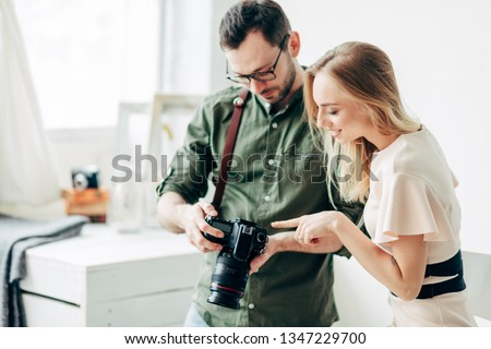 cheerful blond girl pointing at the camera while looking through the photos in the digital camera. close up photo. copy space #1347229700