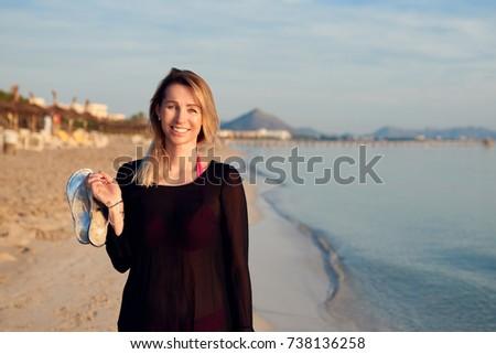 Cheerful blond woman walking along tropical sea beach at sunset