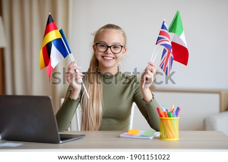 Cheerful blonde teen girl with glasses sitting at workdesk with international flags, home interior, using laptop, studying foreign languages. International education, online language courses