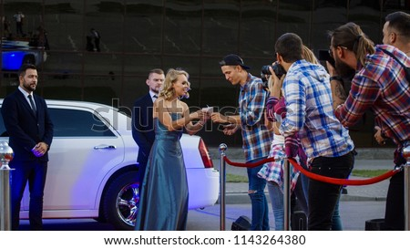Cheerful blonde woman in gray dress getting out of limousine and giving autographs to fans on red carpet