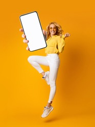 Cheerful blonde woman jumping up and showing newest smartphone with empty screen, enjoying new application for mobile device. Orange studio background, creative collage with mockup