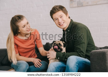 cheerful blonde woman looking at happy man while sitting with cute pug dog on sofa