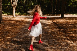 Cheerful blonde woman walking and capering among fallen leaves. Beautiful girl wearing red sweater and stylish shoes.