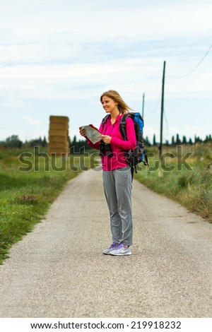 Cheerful blonde woman with backpack  is looking at her map  which way to go,Orientation