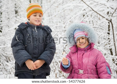 cheerful boy and little girl with Bengal fire in hand in winter in wood