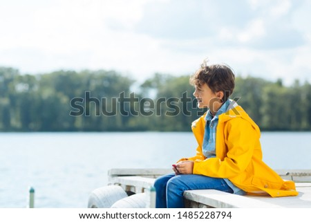 Cheerful boy. Cheerful boy wearing yellow raincoat sitting near river and breathing fresh air #1485228794