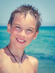 Cheerful boy enjoying summer day on a beach toned