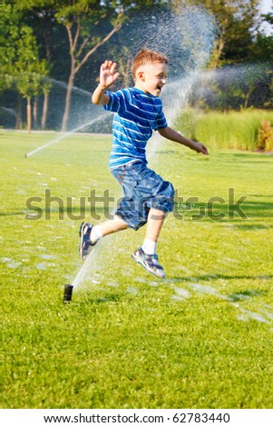 Cheerful boy having fun running from sprinkles