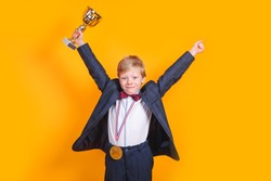 Cheerful boy holding a golden trophy and gold medal on yellow background