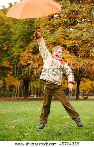 Cheerful boy in autumn park. Has jumped with orange umbrella over head.