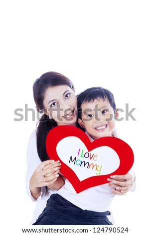 Cheerful boy is giving a love card to his mother on white background