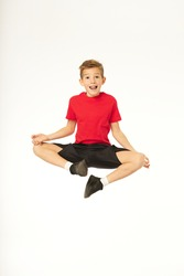 Cheerful boy jumping and doing yoga exercise