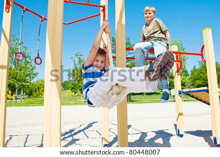 Cheerful boy swinging on rope