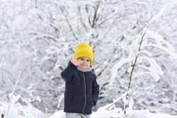 Cheerful boy waving his hand to camera, hello hi concept. Cute little funny child in colorful winter clothes having fun with snow outdoors. Active outdoors leisure with children in winter