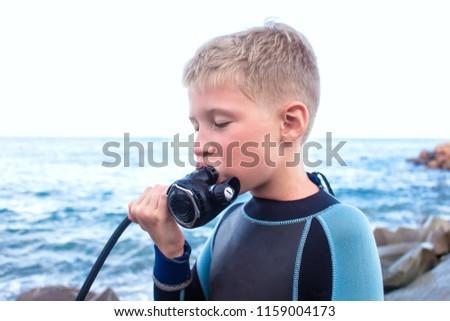 cheerful boy with blond hair breathes through a diving balloon #1159004173