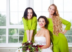 Cheerful bride with bridesmaid holding bouquet indoors